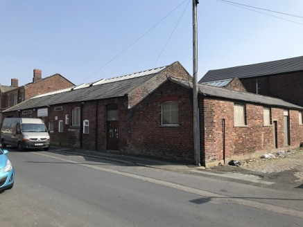 The property comprises of a series of older single storey buildings, of brick evaluations set beneath a pitched double span slate roof, incorporating roof lights, set upon a steel truss roof structure.  The property originally formed three separate b...