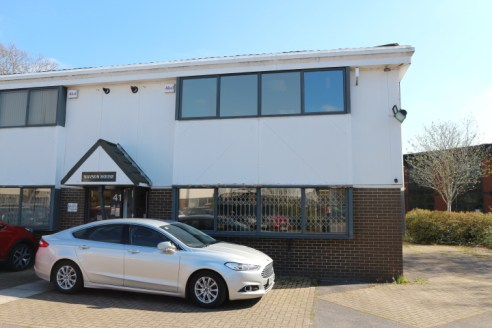 Modern semi-detached, two-storey, open-plan office building with parking.