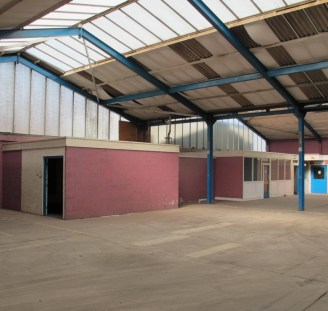 p>\n The site has side access via secure steel gates to the manufacturing/warehouse unit via a service road with tandem parking spaces to the side of the road. This unit is constructed of three portal frame bays with corrugated roof sheets, clear roo...