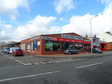 The property comprises a former car showroom of steel portal frame construction clad in brick and incorporating glazing to the front and side aspects, beneath a pitched, asbestos roof. To the rear there is a workshop of similar construction with an o...