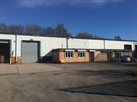 The property forms a mid-terrace single-storey warehouse with good quality and substantial ancillary offices. To the front of the building there is a yard secured by steel electric gates.  The warehouse is of steel portal frame construction, having b...