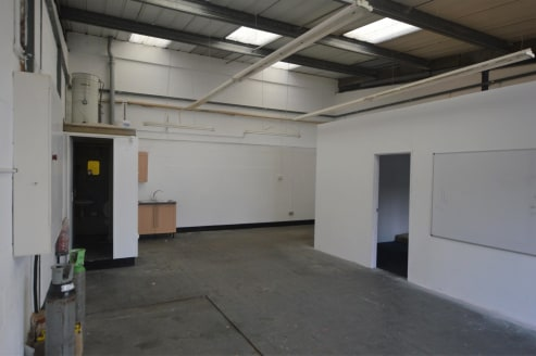 The property comprises a mid-terrace unit of steel frame construction with blockwork walls under a mono-pitched roof with glazed front elevation together with manual up and over loading door. There are 2 car parking spaces to the front of this unit.