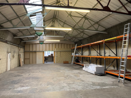 The property comprises a mid-terrace single storey industrial unit of brickwork construction under a pitched asbestos sheet roof. Externally, the property benefits from a loading area and parking spaces to the front.