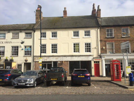 The property comprises a large ground floor retial unit within a three storey mixed commercial and residential building. The main sales area is predominantly open plan with frontage on to Market Place. To the rear of the property are stores kitchen a...