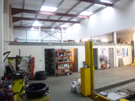 The property comprises a modern warehouse premises with a double storey section to the front and single storey section to the rear plus a large forecourt. The warehouse is of steel portal frame construction with brick elevations beneath a pitched ste...