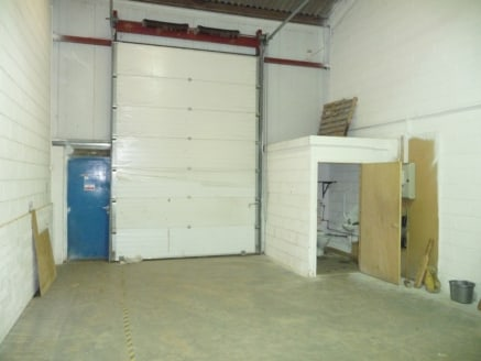 p>\n A mid terraced light industrial unit of some 1,269 sq ft GIA (118.02 m2) with roller shutter door and separate access door, block work walls, clad ceiling with roof lights and sodium lighting, concrete slab flooring and partitioned office of 145...