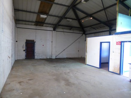 The property comprises a modern single storey industrial unit of steel portal frame construction with brick/blockwork base walls and metal profile sheet cladding above and to the rear which is insulated. The unit has a full height up and over loading...