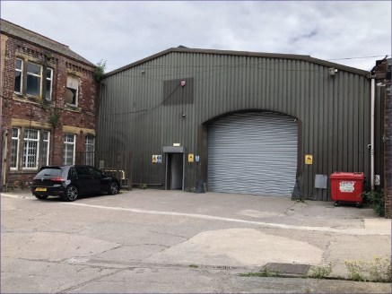 The unit comprises two connecting single storey industrial buildings of brickwork construction, beneath pitched roofs incorporating patent glazing and translucent rooflights, supported on light steel trusses. Under truss heights of approximately min....