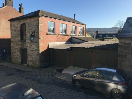The property was previously used as a saw mill. This is a two storey stone fronted property with brick side elevations set beneath a timber framed roof clad in slate. There are two separate lock up garages adjacent with corrugated roofs, brick walls...