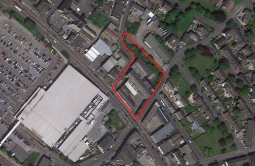 The site is largely rectangular although protruding to the north west corner, and is situated on a site which slopes upward from Bradford Road towards the rear of the site. The site is presently occupied by Victoria Works.