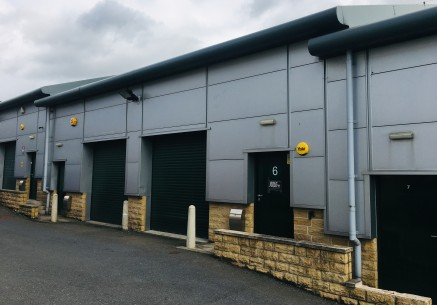 The property comprises an industrial unit within a small terrace of similar industrial units constructed on a steel portal frame being clad in artificial stone with sheet cladding above, under a sheet metal clad roof incorporating translucent panels....