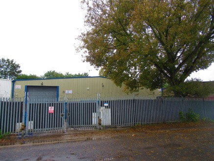 The premises is a single storey, light industrial/warehouse property within a fenced plot.\n\nVehicular access is via a full height roller shutter with personnel door leading directly into the office block.\n\nA front yard is currently used for stora...