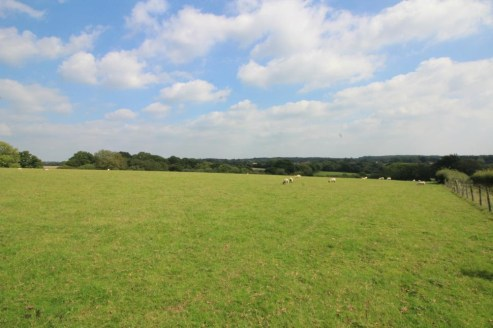 A parcel of gently sloping, predominantly south-east facing agricultural land divided into hedge and fence enclosed pasture fields with a small woodland shaw. Lane Frontage - mains water - no public footpaths. In all about 43.5 acres (17.6 ha).