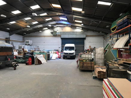 The property comprises a semi-detached industrial unit of traditional steel portal frame construction underneath a pitched roof. The unit has a concrete apron fronting the access road with space for external storage/vehicle parking. The unit is acces...
