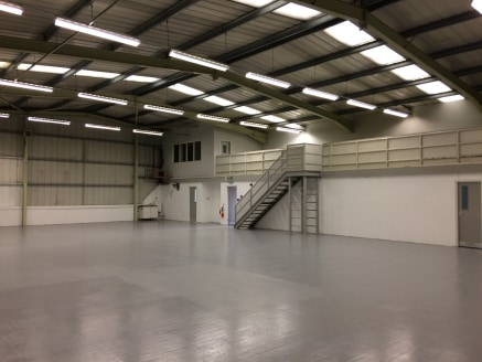The property is an end terraced unit of steel portal frame construction with brickwork/block work walls to approximately 2 m and insulated profile metal walls with pitched roof and translucent roof lights. The warehouse is served by an up and over se...