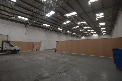 The unit is of steel portal frame construction with brick elevation and steel profile cladding. The unit benefits from a roller shutter door and loading area with first floor offices and yard / car parking to the front.