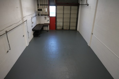 A traditional mid-terrace industrial / warehouse unit with large loading door and onsite car parking.