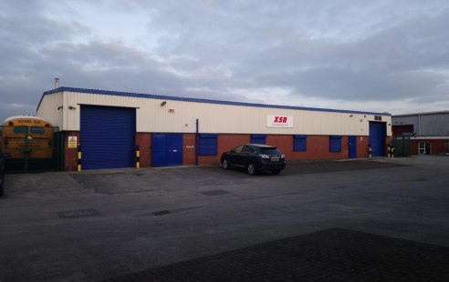 Detached steel portal frame industrial building with parking and secure yards. Currently fitted as vehicle workshop.