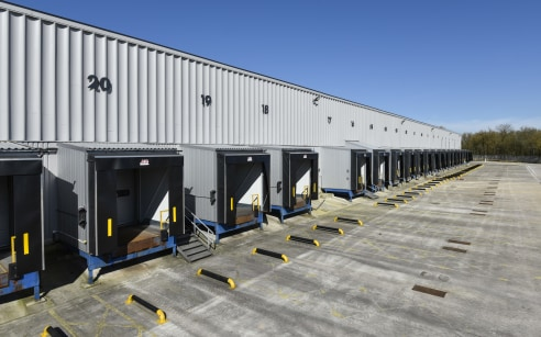 Electrically operated sectional loading. Service yards and car parking. Office area including reception, private offices. Male and female WC's. Security lodge and barrier control at site entrance.