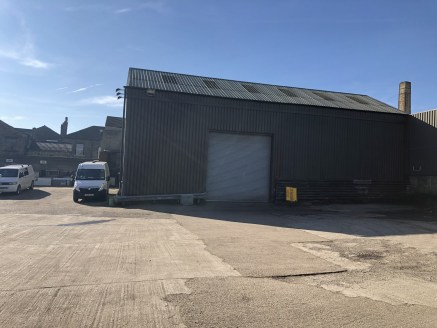 The property comprises a secure yard/compound with two connected workshop units each having drive-in roller shutter loading access, a separate single storey workshop also having drive-in roller shutter door access, storage building and two storey sho...