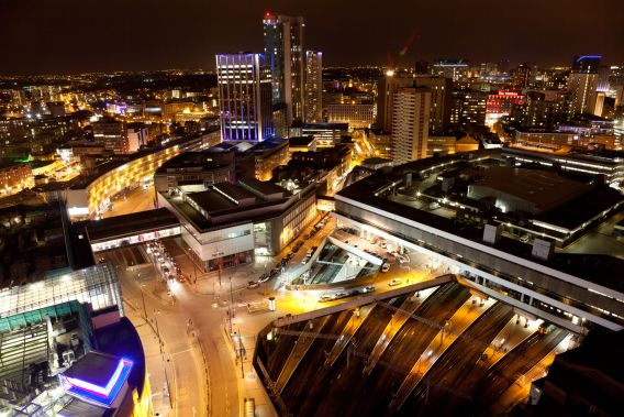An aerial photograph of Birmingham New Street Station taken at night, with the city's skyline in the background