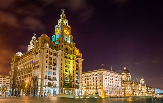 A photograph of the Three Graces building in Liverpool, which is lit up by coloured lights, at night