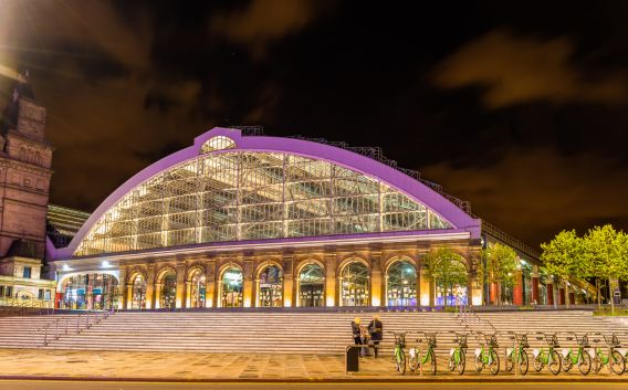 A photograph of the exterior of Liverpool Lime Street station taken at night. The station is illuminated.