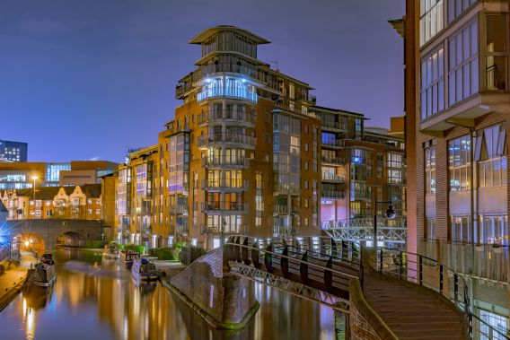 A photograph of the new build property around, and bridges over the, Birmingham canals, as well as some barge boats.