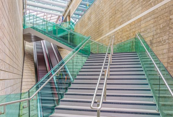 Image of a wide modern staircase, with green glass sides