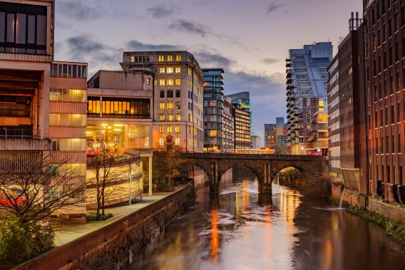 A photo of Manchester's canal and surrounding buildings, taken at dusk