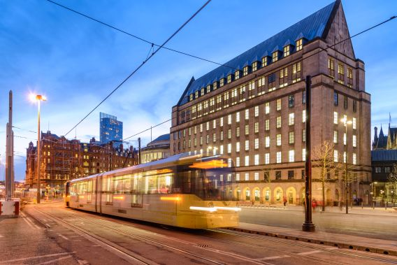 A photolapse image of a tram traveling through Manchester at dusk