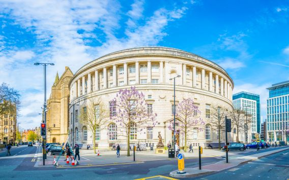 Picture of Manchester library, a circular grand sandstone building, on a clear day