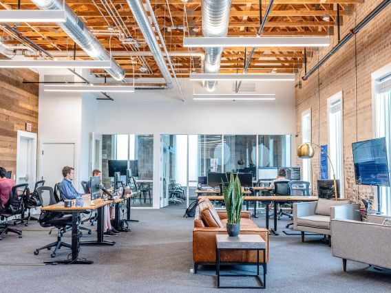 Modern interior of an office space with coworkers sitting next to each other at minimalist desks