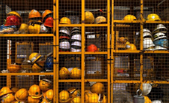 Image of yellow safety helmets in a cage