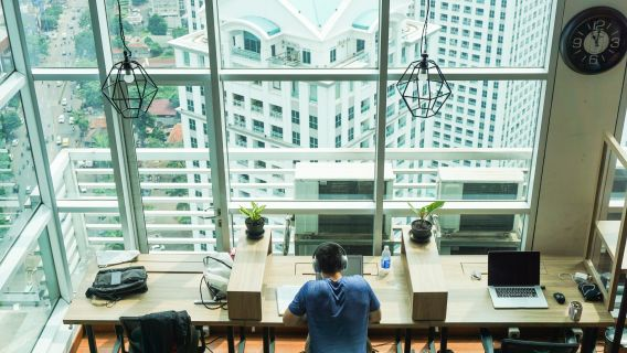 Image of a man working in a modern office space overlooking windows