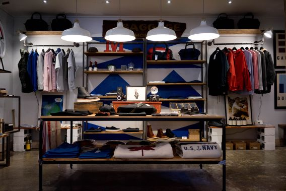 Image of an upscale clothing store with clothes laid out on a shelving unit