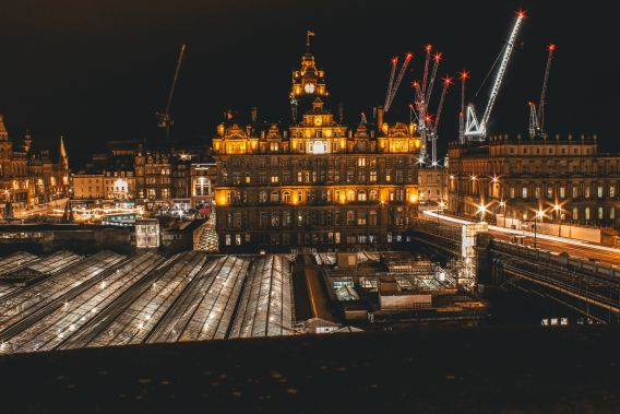 Image of Edinburgh Waverley station at night, with the station lit up