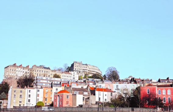 Photo of colourful houses in Bristol on a hillside against a blue sky