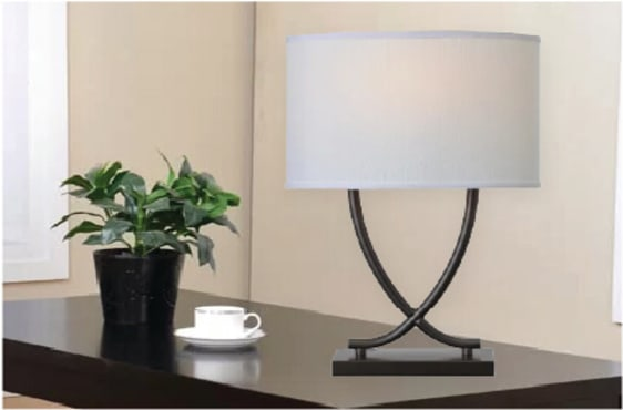 Sculptural graphite table lamp on a black table next to a fake plant and a cup of coffee.