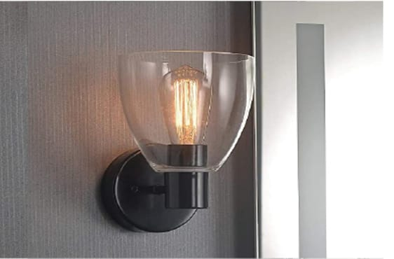 A wall light with a black base and clear glass shade, lit with an Edison-style bulb.