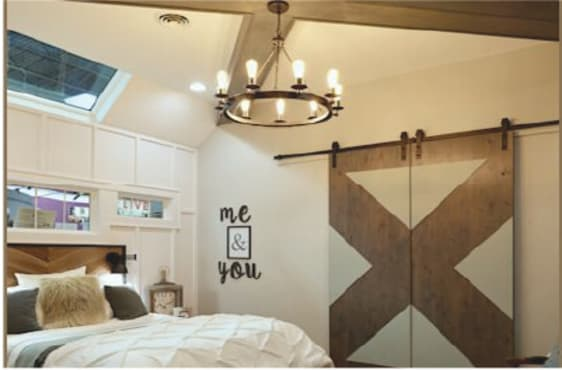 Rustic farmhouse-style bedroom with a wreath-style hanging light fixture, rolling barn doors, and exposed wood ceiling.
