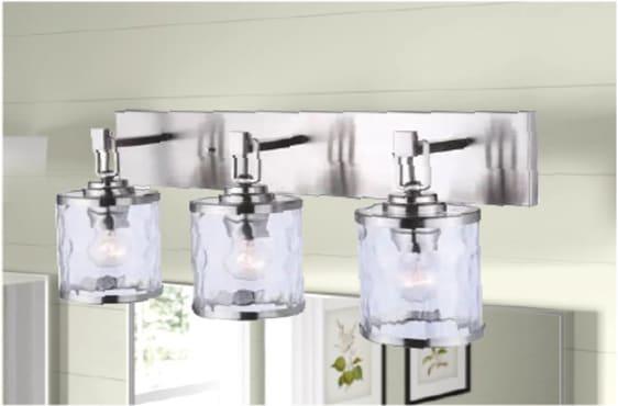 Chrome light fixture above a bathroom mirror with 3 bulbs in 3 cloudy, cylindrical shades.