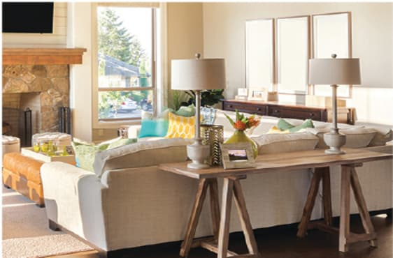 Warmly-colored family room with two long-necked table lamps behind beige sectional sofa.