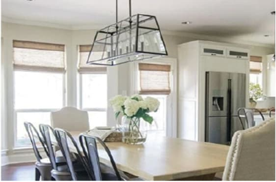 Dining room with hanging light over a blond wood table.