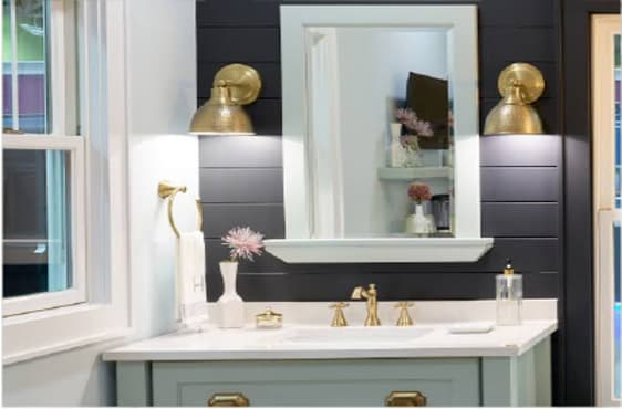 Bathroom sink and mirror with a metal sconce on each side of the mirror.