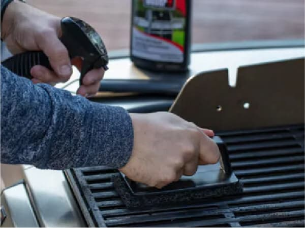 A person with a steel scrubber uses a Weber cleaning product to clean inside the Weber grill Weber Smoker Box