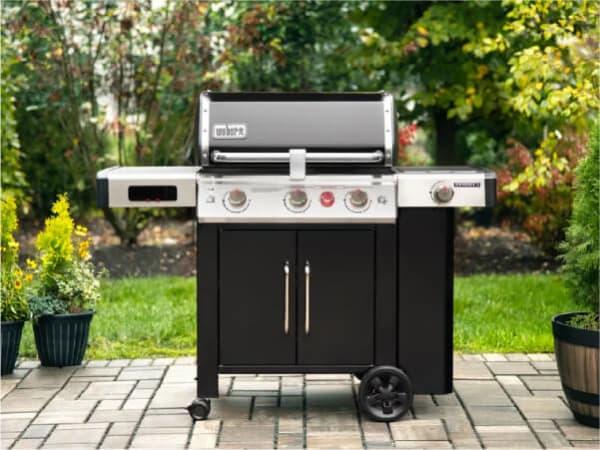 A Weber Genesis II gas grill sits on a backyard patio