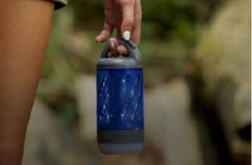 A person stands with a Skeeter Hawk Personal Mosquito Zapper & Lantern dangling from their fingers while hiking through woods