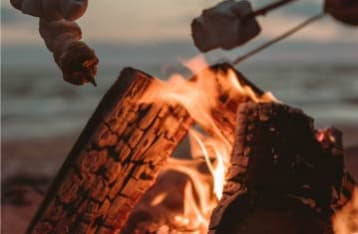 People roast marshmallows over a flaming wood fire pit
