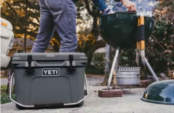A YETI cooler sits in the foreground while a person uses a smoking kettle grill in the background.